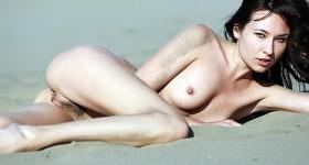 nude-brunette-having-fun-at-the-beach